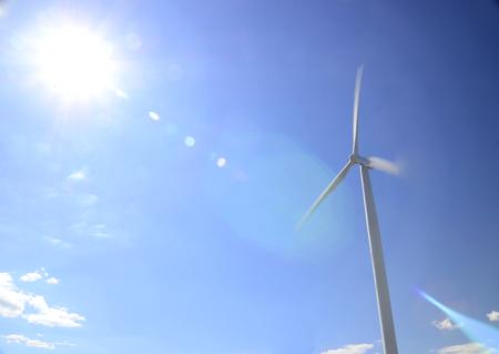 The bright sun shines above a hawt wind turbine against a vast sky