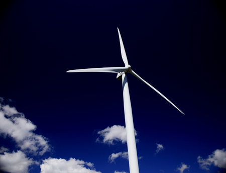 horizontal image of a Hawt wind turbine against a slate blue sky
