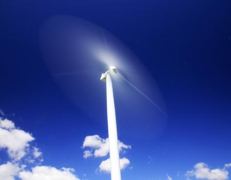 Wind turbine in motion against a regal dark blue sky guarded below by splendid white clouds.