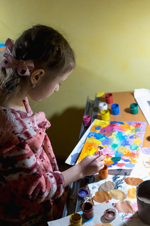 Cute little girl painting with paintbrush and colorful paints in home interior.