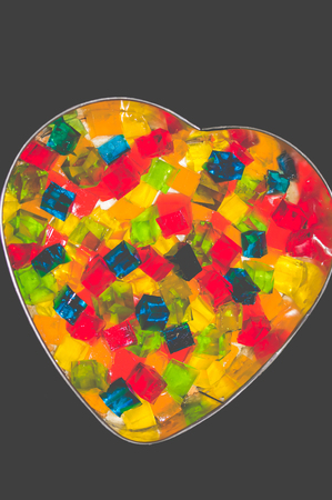 Photo pour Jelly cake in the form of a heart with multi-colored cubes in the middle. The cake is being prepared - image libre de droit