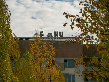 Decaying residential building with a part of signpost in russian language. Only part of word visible and letters F,N,N,Y. Pripyat ghost city. Ukraine