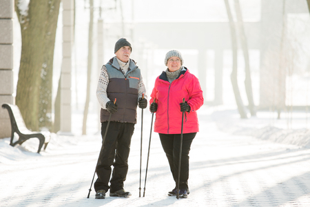 Photo pour Senior couple walking with nordic walking poles in winter park. Mature woman and old man doing exercise outdoors. Healthy lifestyle concept. - image libre de droit