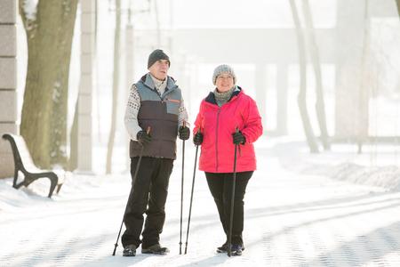 Foto de Senior couple walking with nordic walking poles in winter park. Mature woman and old man doing exercise outdoors. Healthy lifestyle concept. - Imagen libre de derechos