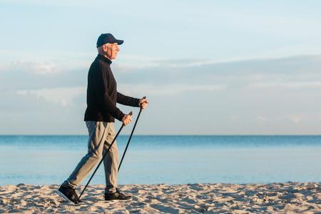 Foto de Nordic walking - senior man working out on beach. Healthy lifestyle - Imagen libre de derechos