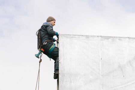 Photo pour Industrial climber repair billboard. Risky job. Work on height. Metal construction. Electric screwdrive. - image libre de droit