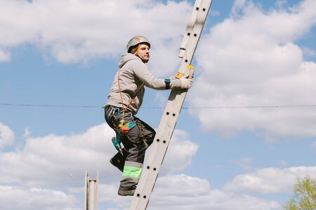 Photo for Industrial climber in helmet and overall working on height. Risky job. Professional worker going up the ladder. - Royalty Free Image