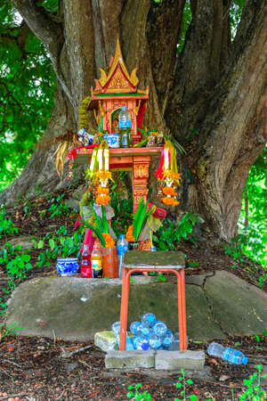 Photo pour A spirit house on earth mound with a huge tree stands behind. Traditional Thai Miniature house built for a guardian spirit to reside. Food and drink are common offerings from Buddhists and worshipers. - image libre de droit