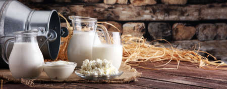 Photo pour milk products. tasty healthy dairy products on a table on. sour cream in a bowl, cottage cheese bowl, cream in a a bank and milk jar, glass bottle and in a glass - image libre de droit