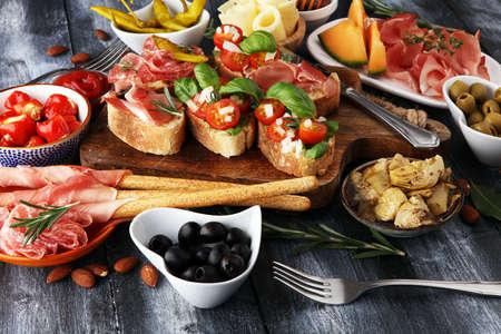 Photo pour Italian antipasti wine snacks set. Cheese variety, Mediterranean olives, pickles, Prosciutto di Parma, tomatoes, artichokes and wine in glasses - image libre de droit