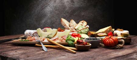 Foto de Italian antipasti wine snacks set. Cheese variety, Mediterranean olives, pickles, Prosciutto di Parma with melon, salami and wine in glasses over black grunge background - Imagen libre de derechos