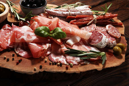 Foto de Marble cutting board with prosciutto, bacon, salami and sausages on wooden background. Meat platter appetizers and olives - Imagen libre de derechos