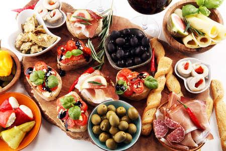 Italian antipasti wine snacks set. Cheese variety, Mediterranean olives, pickles, Prosciutto di Parma, tomatoes, artichokes and wine in glasses on table