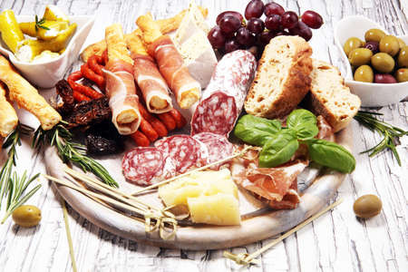 Foto de antipasto various appetizer. Cutting board with prosciutto, salami, coppa, cheese, bread sticks and olives on white wooden - Imagen libre de derechos