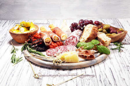Foto de antipasto various appetizer. Cutting board with prosciutto, salami, coppa, cheese,bread sticks and olives on white wooden - Imagen libre de derechos
