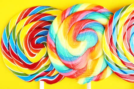 Foto de lolly candies with sugar. colorful array of childs lollipops sweets and treats on yellow - Imagen libre de derechos