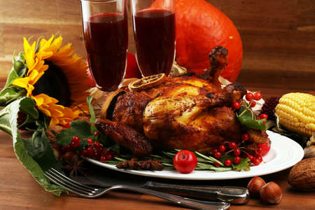 Photo for Baked turkey or chicken. The thanksgiving table is served with a turkey, decorated with fruits, salad and nuts. Fried chicken, table. Thanksgiving dinner - Royalty Free Image