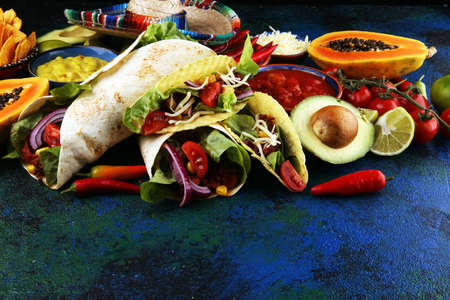 Photo pour Mexican food, including tacos, guacamole, nachos and pepper on table - image libre de droit