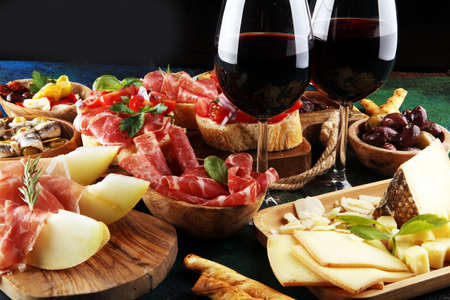 Photo for Italian antipasti wine snacks set. Cheese variety, Mediterranean olives, pickles, Prosciutto di Parma, tomatoes, anchovy and wine in glasses over black grunge background - Royalty Free Image