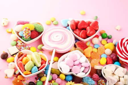 Photo for candies with jelly and sugar. colorful array of different childs sweets and treats on pink - Royalty Free Image