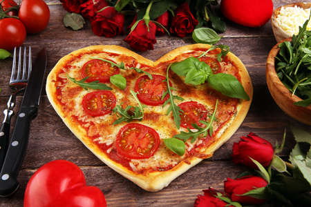 Photo pour pizza Heart shaped margherita with tomatoes and mozzarella vegetarian. Food concept of romantic love for Valentines Day. - image libre de droit
