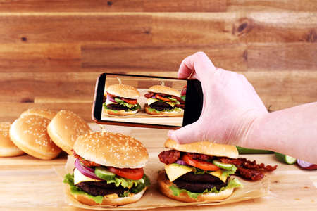 Photo for takes a picture smartphone eating fast food. Delicious homemade burgers. Tasty fresh meat burgers with salad and cheese.  - Royalty Free Image