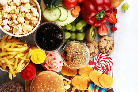 Photo for healthy or unhealthy food. Concept photo of healthy and unhealthy food. Fruits and vegetables vs donuts,sweets and burgers on table - Royalty Free Image