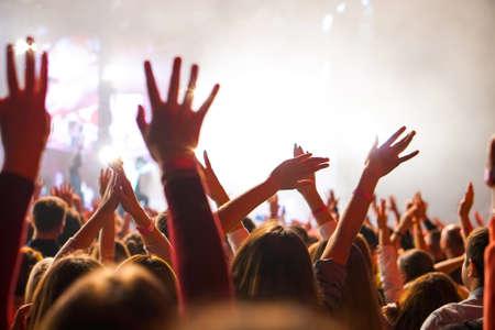 Photo pour Crowd at a music concert, audience raising hands up - image libre de droit