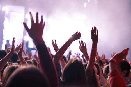 Photo pour crowd cheering and hands raised at a live music concert - image libre de droit