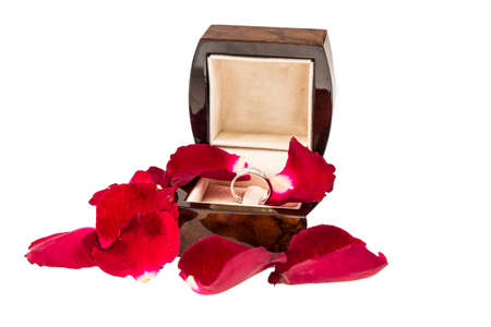 Red rose petals  with diamond ring on white