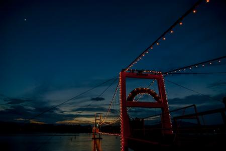 The old wooden bridge Bridge collapse bridge Rattanakosin suspension bridge across the Ping river and Wood bridge Mon bridge sunset at Tak Province, thailand