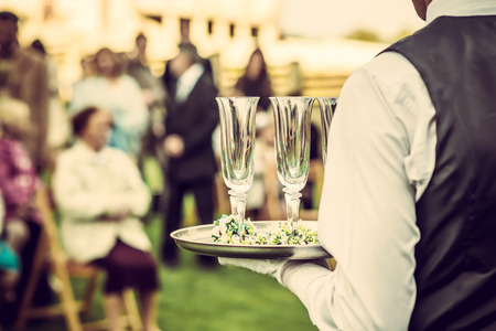 Waiter with glasses on the tray at wedding ceremony, waiting for champagne