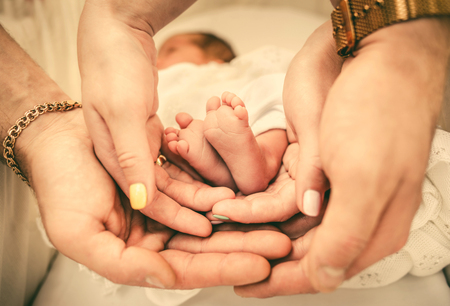 Photo pour Newborn baby feet in parents hands - image libre de droit