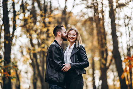 Photo for Sunny portrait of a young loving couple walking in the autumn park. They hug and smile, enjoy a walk. - Royalty Free Image