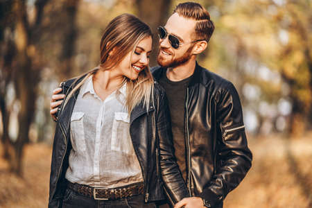 Photo pour Sunny portrait of a young loving couple walking in the autumn park. They hug and smile, enjoy a walk. - image libre de droit