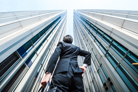 Photo pour Businessman looking up at the high building, low angle - image libre de droit