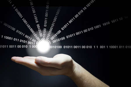 Hand holds a glowing ball emitting data streams