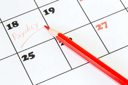Red pencil on a calendar with the word Payday written on one of the days