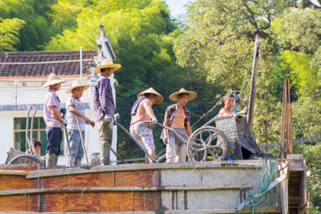 Likeng,China - Construction workers with straw hats working on a roof with traditional tools emptying a cart with concrete