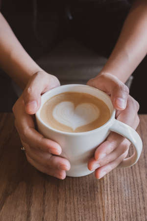 Photo for Hand holding a cup of coffee with heart foam milk. - Royalty Free Image