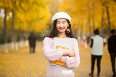 Portrait of a smiling pretty woman holding a book on an autumn  day