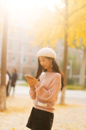 Portrait of a smiling pretty woman texting on an autumn day
