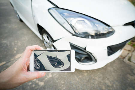 Man taking photo of damaged white car with smartphone