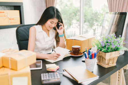 Young Asian small business owner working at home office, using mobile phone and taking note on purchase orders. Online marketing packaging delivery, startup SME entrepreneur or freelance woman concept