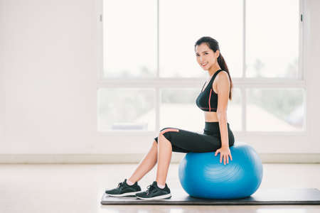 Sexy young Asian girl exercise, smile on fitness ball at clean home gym, sports club. Yoga aerobic class, sport trainer, weight loss, fat burn, or healthy wellbeing lifestyle concept. With copy space