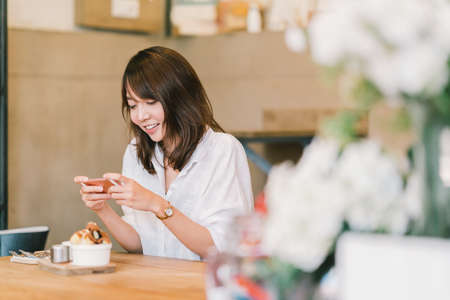 Foto de Beautiful Asian girl taking photo of sweet desserts at coffee shop, using smartphone camera, posting on social media. Food photograph hobby, casual relax lifestyle, modern social network habit concept - Imagen libre de derechos