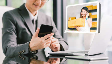 Businessman CEO order product box from young female Asian small business owner using phone, laptop. Online marketing shipping delivery service, e-commerce technology, or telemarketing startup SME