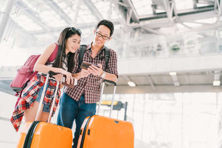 Foto de Asian couple travelers using smartphone checking flight or online check-in at airport, with passport and luggage. Air travel or mobile phone technology concept - Imagen libre de derechos