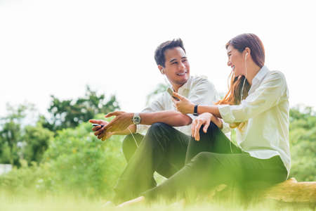 Foto de Young Asian lovely couple or college students sit listening to song music on smartphone together in park. Leisure activity, Online love, internet dating app technology, or casual lifestyle concept - Imagen libre de derechos