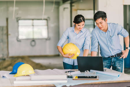 Photo for Young Asian engineers couple work together using notebook computer at building construction site. Civil engineering brainstorm meeting, architecture design, or house builder concept. With copy space - Royalty Free Image